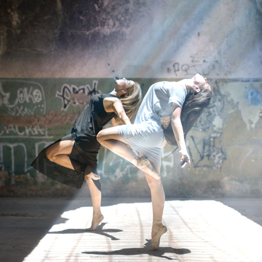 two girls dancing under a ray of light